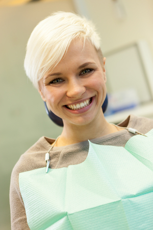 portrait of smiling blonde woman at the dentist photo