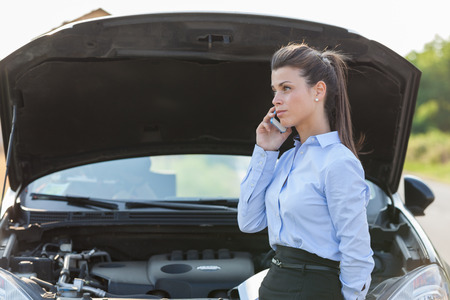 Photo of caucasian businesswoman standing next to her car and calling assistance for car problems