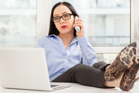 Photo of caucasian businesswoman phoning in the office with legs on the desk Stock Photo