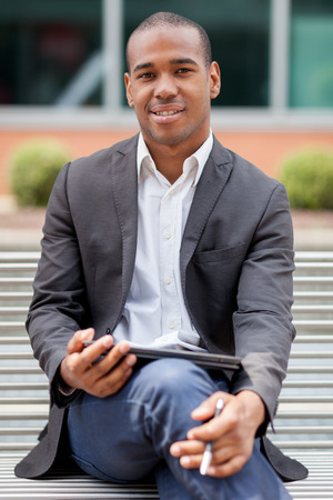 freelance: Photo of handsome african businessmman sitting on a bench with tablet pc and pen Stock Photo