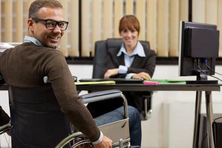 fotografie usmívající se muž na invalidním vozíku při pohledu do kamery, zatímco žena manažer sedí na židli v pozadí