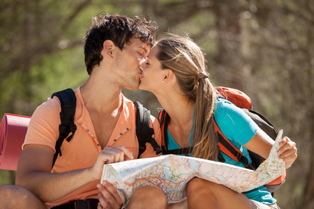 in kiss: Photo of young couple sitting on a big rock in the mountains and kisses each other Stock Photo