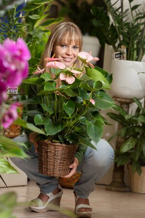 houseplant: photo of smiling caucasian woman choosing a plant in a flower shop