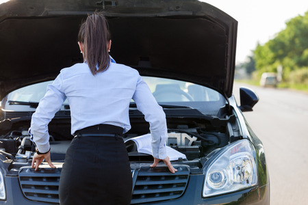 Caucasian businesswoman looking inside the car hood Stock Photo