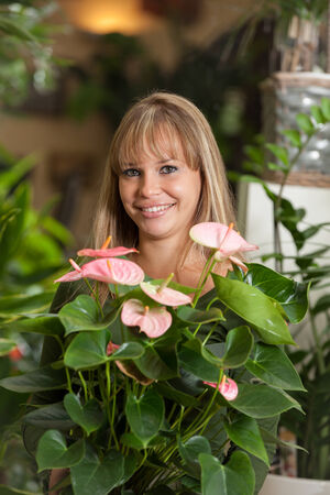 houseplant: smiling caucasian woman choosing a plant in a flower shop Stock Photo