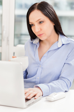 �aucasian: Photo of aucasian businesswoman working with notebook while drinking coffee in the office