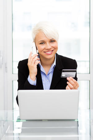 Caucasian blonde woman is online shopping with credit card and phone in office photo