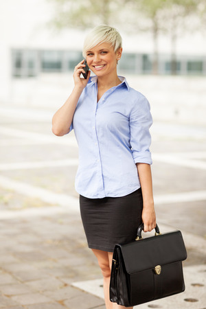 Portrait of caucasian blonde businesswoman standing outdoor with bag and phone photo
