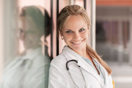 Portrait of smiling female doctor standing next to glass wall photo