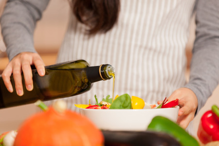 Closeup of woman pouring olive oil into the colorful salad Standard-Bild