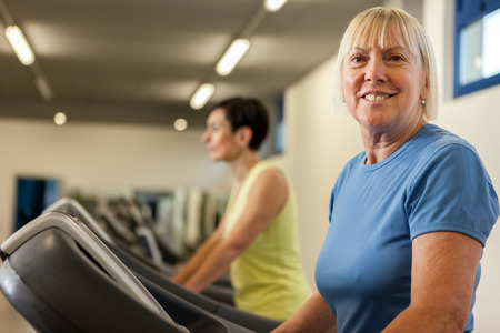 looking towards camera: Portrait of caucasian mature woman looking towards the camera while running on a treadmill in the fitness studio Stock Photo