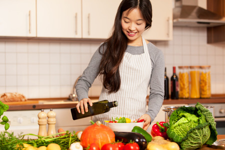 Photo of asian smiling woman pouring olive oil into the colorful salad Stockfoto