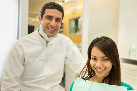 looking towards camera: photo of smiling caucasian dentist sitting next to his female patient and looking towards the camera Stock Photo