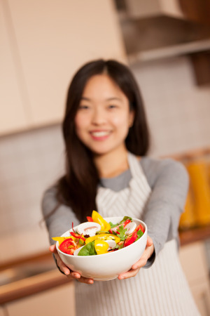 korean food: photo of asian smiling woman holding a colorful salad in her hands in the kitchen Stock Photo