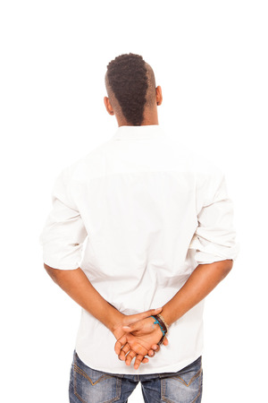 hands behind back: African man looking at the white wall with crossed hands behind his back over white isolated background