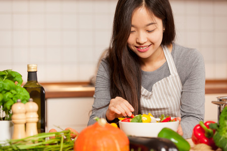 photo of asian young woman composing a colorful salad at home in the kitchen Stockfoto