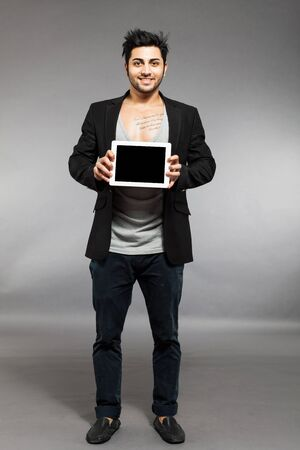 Caucasian man is standing with digital touch screen over grey background photo