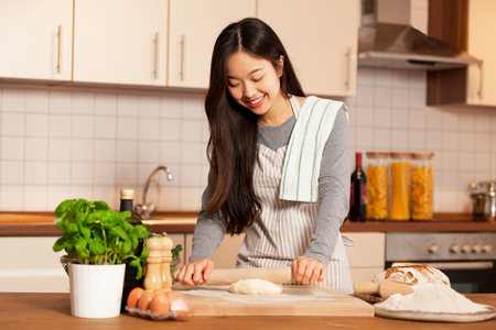 Asian smiling woman is baking bread in her home kitchen