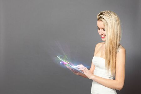 woman tablet pc: Blonde caucasian woman standing with tablet over grey background