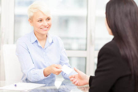 businesswoman card: Businesswoman giving her business card to another businesswoman in office