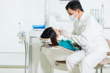 男性アジア歯医者 diong 歯科が歯科医のオフィスで若いアジア女性に検診の写真