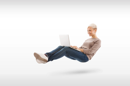 Blonde relaxed woman with notebook on her legs over white isolated background photo