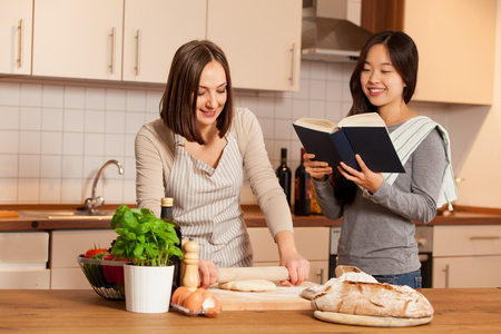Woman is working on a dough while her friend is reading a cookbook Stock Photo