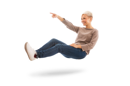 Casual dressed woman is floating while indicating a direction over white isolated background