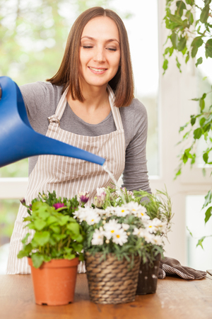 smiling woman in a greenhouse: Caucasian smiling woman is pouring water in the plants