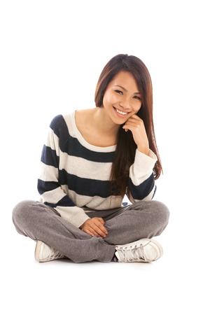 persona sentada: Muchacha asiática sonriente sentado en el suelo sobre fondo blanco aislado