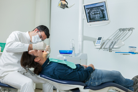 40 years old man: photo of european male dentist doing a checkup on a 40 years old man