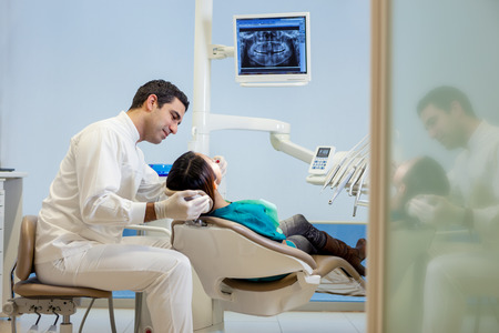 stockphoto: stockphoto of male dentist taking a plaster model from a young asian patient