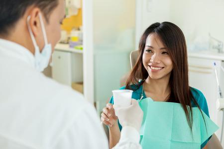彼女は歯科医から水のガラスを取っているアジアの女性を笑顔 写真素材