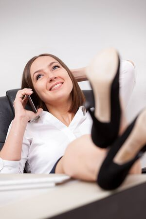 table skirt: Caucasian businesswoman with legs on the desk is phoning in her office Stock Photo