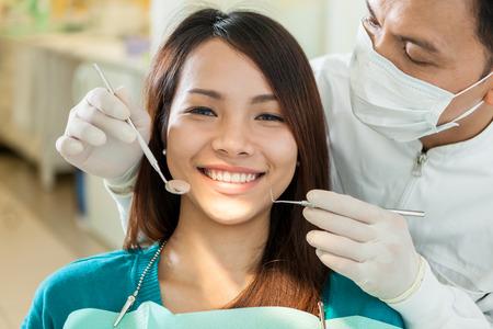 치과 의사에 앉아 웃는 아시아 여자의 초상화