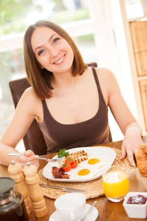 bacon portrait: Portrait of smiling young woman having breakfast at home Stock Photo