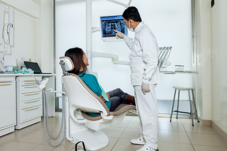 Asian dentist is showing X-ray on a screen to his patient