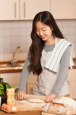 baking bread: Asian woman is baking bread in her home kitchen
