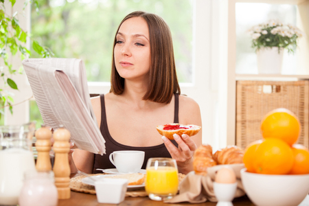 periodicos: Atractiva mujer está leyendo el periódico mientras desayuna en casa