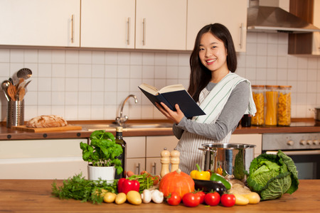 Asian smiling woman looking a cookbook while standing in her kitchen 写真素材