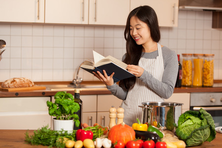 Asian smiling woman looking a cookbook while standing in her kitchen Standard-Bild
