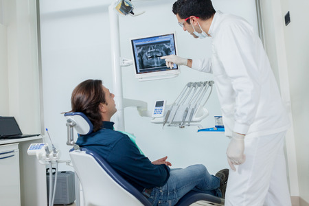 Dentist is showing his patient on the monitor what he is going to do