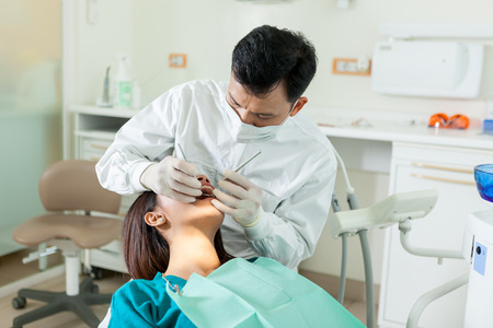 photo of male asian dentist diong a dental check up to a young asian woman in a dentist office photo