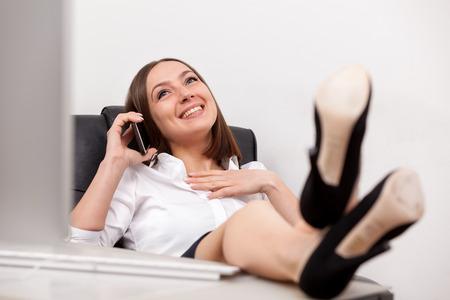 pies sexis: Foto de empresaria sonriente morena con las piernas sobre el escritorio llaman por teléfono en la oficina