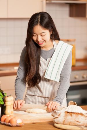 アジアの女性は彼女の家の台所でパンを焼く