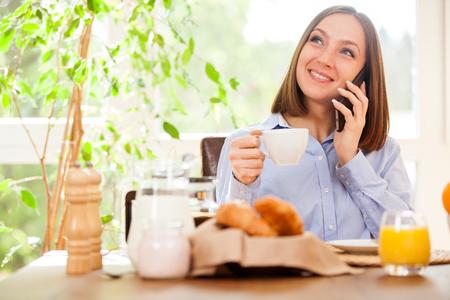 Photo of smiling brunette businesswoman phoning while having breakfast Stock Photo