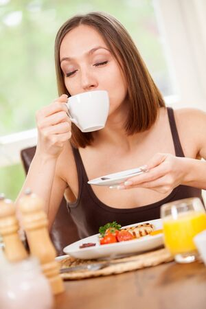 bacon portrait: Young woman is drinking a hot cup of coffee while having a breakfast at home Stock Photo
