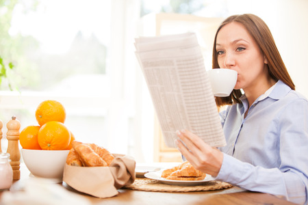 Brunette businesswoman is reading the newspaper while having breakfast at home photo