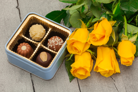 praline: Photo of chocolate pralines with flowers over wooden table Stock Photo