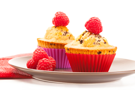 Photo of cupcakes with raspberries over white isolated background